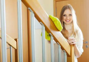 woman dusting  railings at home
