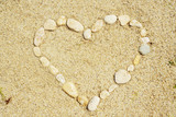 heart shaped with stones on sand background