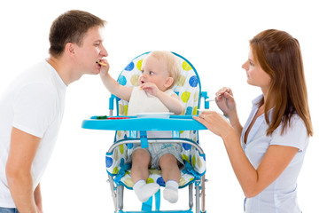 Young parents feed  baby.