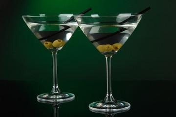 Martini glasses with olives on dark green background