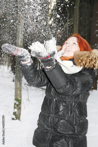 Happy girl in black jacket throws up snow in woods at winter.