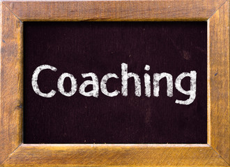 """Coaching"" ; , handwritten with white chalk on a blackboard"