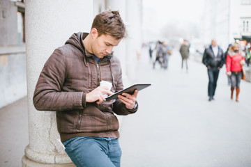 Young man drinking coffee on the street and using tablet compute
