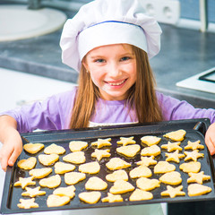 little girl holding a baking sheet of cookies