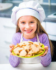 little girl holding a bowl with cookies