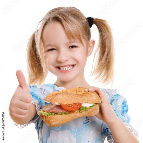canvas print picture lachendes Kind hält Daumen hoch zu gesunder Ernährung