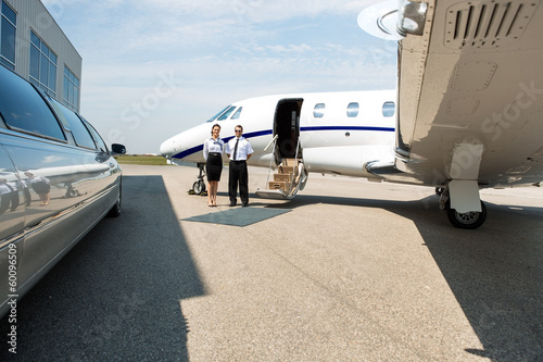 Stewardess And Pilot Standing Neat Limousine And Private Jet