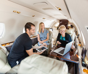 Business People Having Discussion On Private Jet
