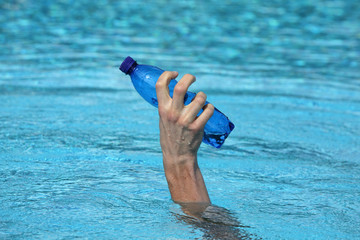 hand raising out of water holding plastic blue bottle of water