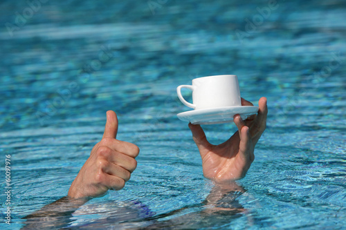 thumb up gesture - hand above water holding cup of coffee