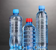 plastic bottles of water on grey background