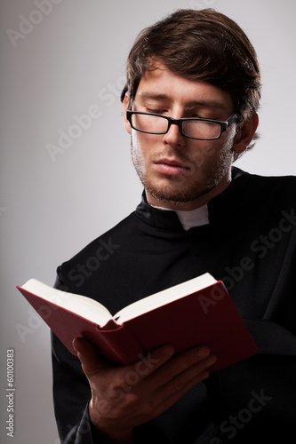 Young clergyman studying a Bible - 60100383