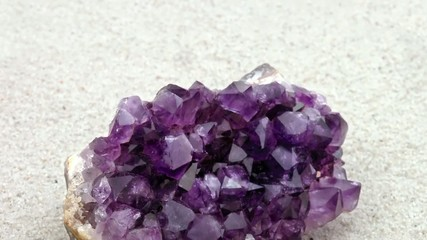 Rough and smooth purple Amethyst crystals on sand