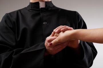 Priest holding believer hand