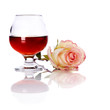 Glass and rose on a white background.