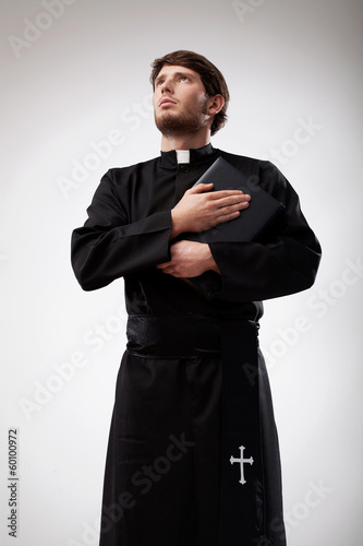 Young priest holding his prayer book - 60100972