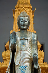 The metal standing Buddha with golden pagoda in the temple in Th