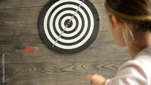 little girl throwing darts at the target, focus on the target