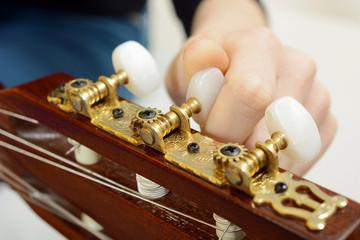 Frau stimmt Gitarren-Saiten