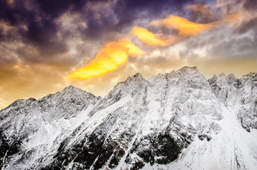 Winter mountains with dramatic colorful sky at sunset