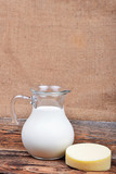 Glass jug with milk and piece of cheese