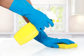 hand with glove using cleaning sponge to clean up
