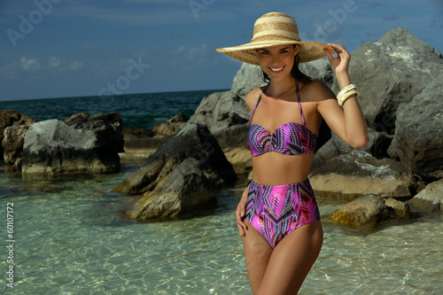 Young woman in straw hat standing in shallow tropical water