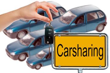 Hand mit Autoschlüssel und Schild - Carsharing