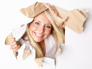 Woman with a smile looking through paper hole