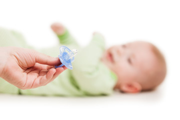 Mother giving soother pacifier to little sleeping newborn baby c