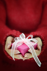 Female hands with long sleeves holding gift box