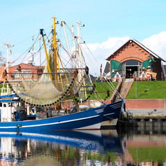 Crabber boat and Cafe in Greetsiel harbor - northern if Germany