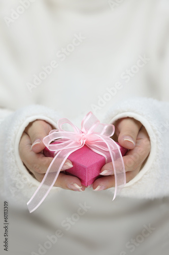 Hands with white long sleeves holding gift wrapped box
