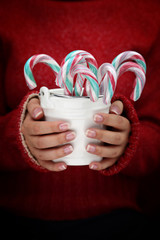 Female hands holding white bucket with candy canes