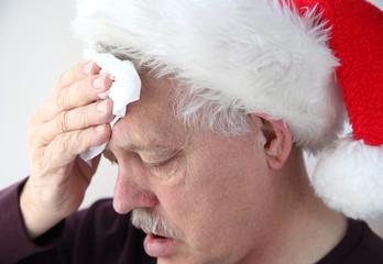 senior in Santa hat mops his brow