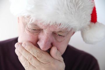 senior in Santa hat has nausea