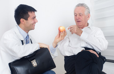 Doctor showing apple to patient