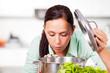 Frau schaut in den Kochtopf