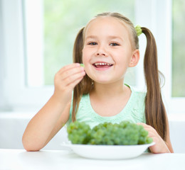 Cute little girl is eating green grapes