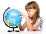Little girl is examining globe