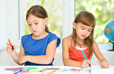 Little girls are drawing using felt- tip pens