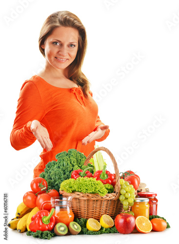 Young woman with variety of organic vegetables isolated on white