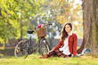 Beautiful female with bicycle sitting in a park and looking at c