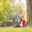 Beautiful young female with bicycle sitting in park and looking
