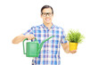 Young man holding watering can and flowerpot