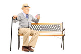 Senile old man with cane, on bench imagining playing cards with