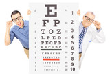 Man and an optician with glasses standing behind eyesight test