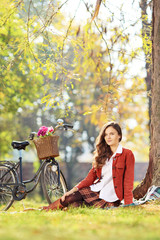 Beautiful young female with bicycle sitting in park