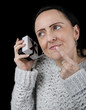 happy woman shaking gift box to guess what is inside