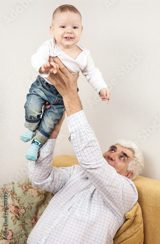 Happy grandfather holding grandson while sitting on sofa